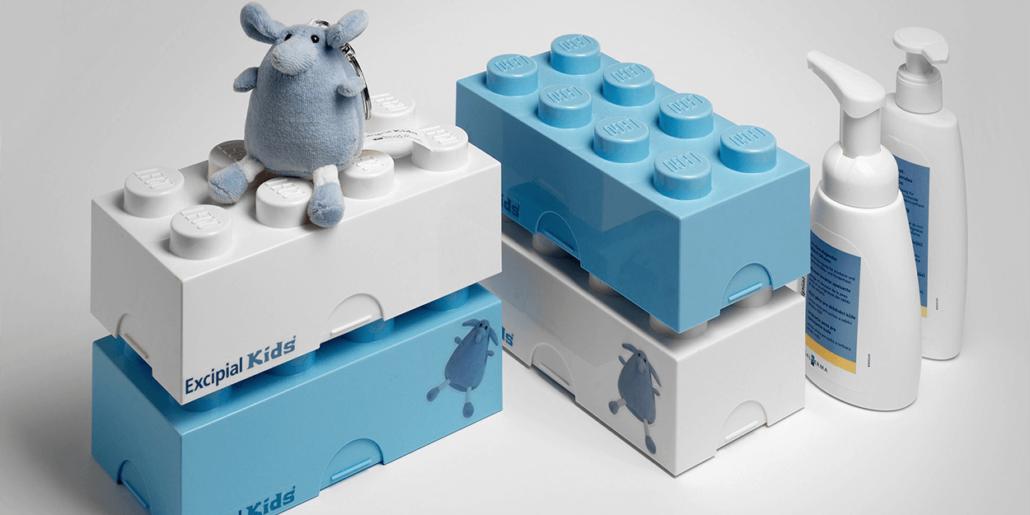 Vier grosse Legosteine, die als Verpackung dienen und ein Schlüsselanhänger mit einem Plüschtier in Form einer Maus.
