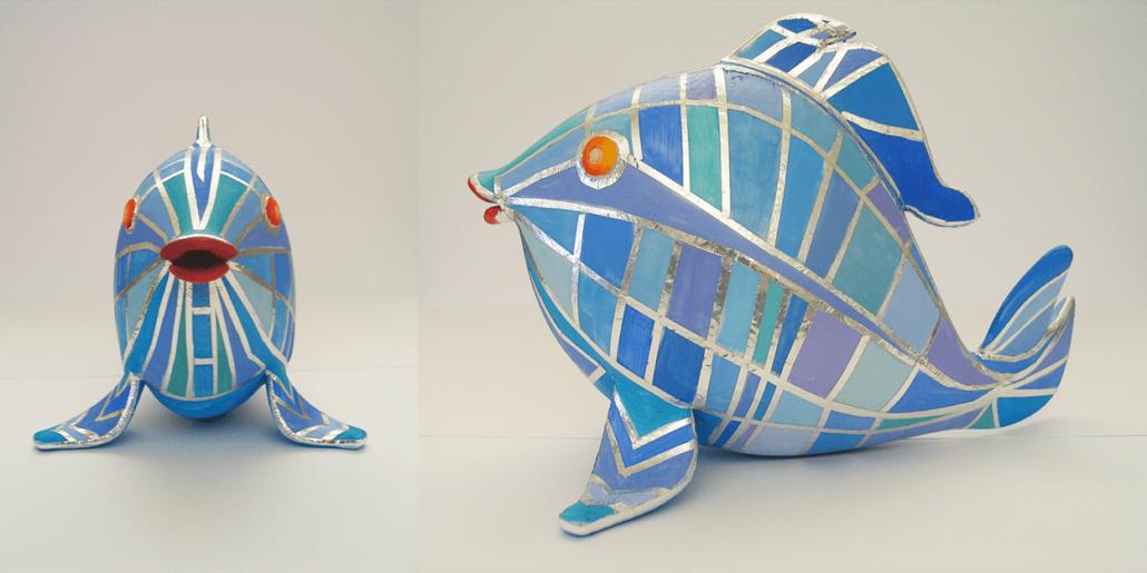 Eine kleine Skulptur von einem Fisch, die in Silber, Blau und Violett bemalt ist. Eine Ansicht von vorne und eine von der Seite.