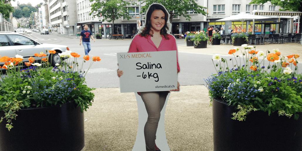 """Ein Pappaufsteller einer Frau, die ein Plakat mit """"Salina -6kg"""" hält."""