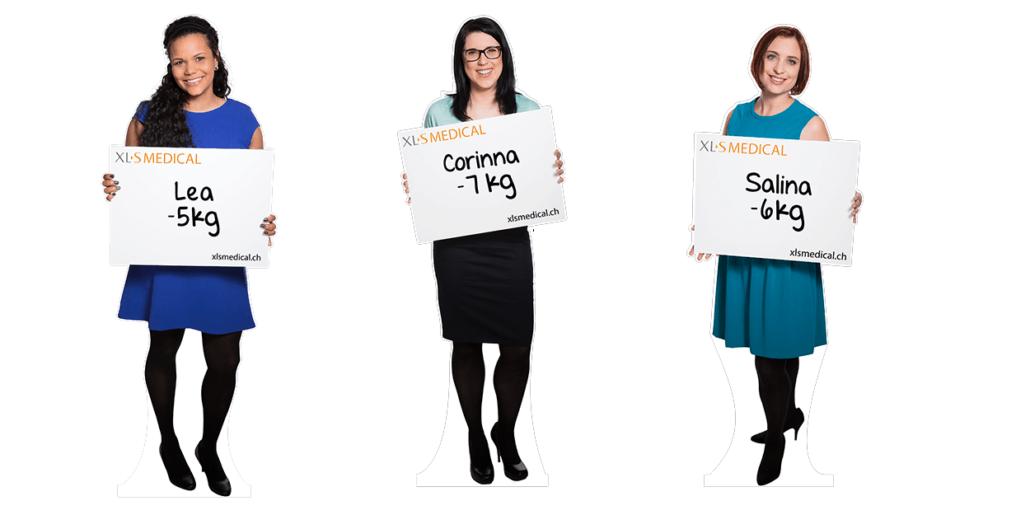Drei Pappaufsteller von Frauen, die je ein Schild in den Händen halten: Lea -5kg, Corinna -7kg und Salina -6kg.